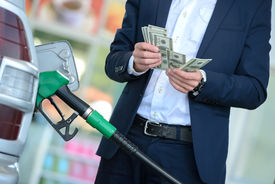 image of fuel economy  - Businessman counting money with gasoline refueling car at fuel station - JPG