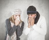 stock photo of sneezing  - Sick couple in winter fashion sneezing against weathered surface - JPG