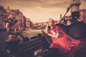 foto of carnival ride  - Beautiful woman in red cloak riding on gondola - JPG