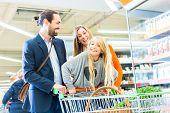 stock photo of caddy  - Family with shopping cart in supermarket store - JPG