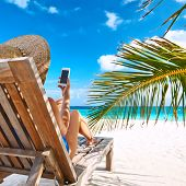 stock photo of beach hat  - Young woman in hat with mobile phone at the beach - JPG