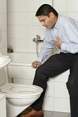 stock photo of puke  - Photo of an adult male in his late thirties with stomach sickness about to vomit into his toilet - JPG