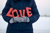 stock photo of down jacket  - Girl in blue down jacket and gloves holding a sign  - JPG