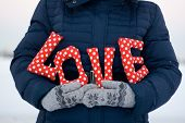picture of down jacket  - Girl in blue down jacket and gloves holding a sign  - JPG