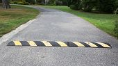 stock photo of bump  - Yellow Striped Speed Bump on asphalt road surrounded with green - JPG