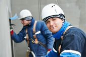 picture of putty  - builders at facade plastering work during industrial building with putty knife float - JPG