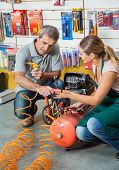stock photo of air compressor  - Saleswoman showing air compressor to male customer in hardware store - JPG
