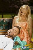 stock photo of lap  - Relaxed smiling casual man laying in lap of happy romantic blonde woman at picnic - JPG