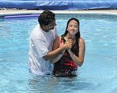 stock photo of minister  - An Asian Indian pastor baptising a preteen in a swimming pool - JPG