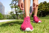 stock photo of japan girl  - Runner getting ready for jogging tying running shoes laces  - JPG
