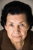 image of nostalgic  - closeup portrait of grandmother looking nostalgic at camera - JPG