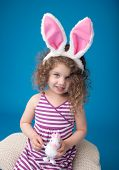 picture of bunny ears  - Happy laughing smiling child girl playing with easter bunny wearing bunny ears looking at camera - JPG
