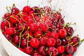 foto of freezing  - Freezed drops of water over the ripe cherries rinsed with water in the white colander - JPG