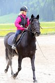 picture of horse girl  - young girl on black horse is learning to ride - JPG