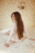 stock photo of bare butt  - Attractive bride Girl model with long brown hair style wearing in white lace sexy lingerie sitting on bed in luxury modern interior - JPG