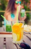stock photo of infusion  - Closeup of infused fruit water cocktail and young woman drinking green vegetable smoothie in the background - JPG