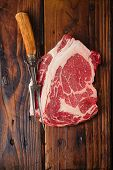 picture of ribeye steak  - raw beef Ribeye  steak   on wooden  table with vintage carving fork - JPG