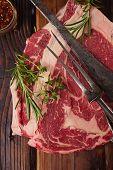 image of ribeye steak  - raw beef Ribeye  steak   on wooden  table with vintage carving fork and knife - JPG