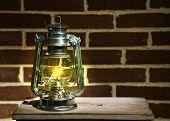 pic of kerosene lamp  - Burning kerosene lamp on brick wall background - JPG