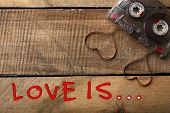 image of heart sounds  - Audio cassette with magnetic tape in shape of hearts on wooden background - JPG