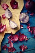 image of red shallot  - halved red onion on a blue wooden background - JPG