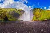 stock photo of waterfalls  - Huge picturesque waterfall flowing from under a giant glacier - JPG