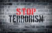 stock photo of isis  - Stop Terrorism stencil print on the grunge white brick wall - JPG