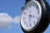 image of puffy  - Face of outdoor clock telling the time of three thirty against a blue sky with white puffy clouds - JPG