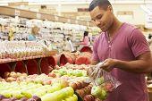 pic of supermarket  - Man At Fruit Counter In Supermarket - JPG