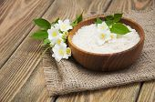 foto of jasmine  - Wooden plate with jasmine rice and jasmine flowers on a wooden background - JPG