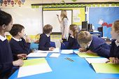 stock photo of 11 year old  - Pupils Sitting At Table As Teacher Stands By Whiteboard - JPG