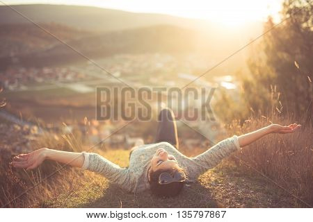 poster of Carefree happy woman lying on green grass meadow on top of mountain edge cliff enjoying sun on her face.Enjoying nature sunset.Freedom.Enjoyment.Relaxing in mountains at sunrise.Sunshine.Daydreaming