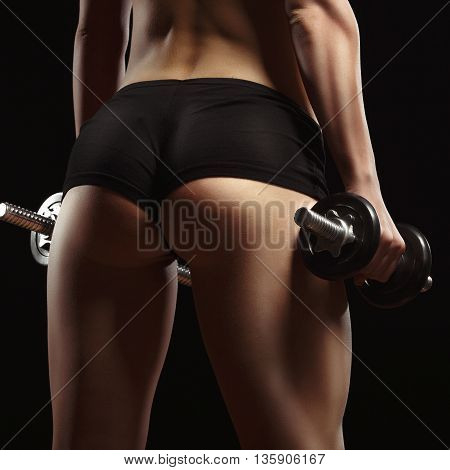 poster of Sexy fitness ass close-up. Part of fitness body on a black background. Perfect female sports figure. Fitness woman posing in the studio. Fitness photo shoot in the studio. Fitness bikini