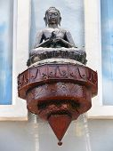 picture of budha  - Cast iron and copper budha lantern against light blue stucco wall - JPG