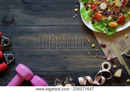poster of Fresh Healthy Salad With Dumbbells, Jump Rope, Tape Measure And Excercise Equipment On Wood Backgrou