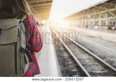 poster of Young Asian Woman Backpacker Traveler Walking Alone At Train Station Platform With Backpack. Asian W