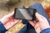 Closeup Photo Man Hold And Watching Video On Smartphone, Horizontal Wide Screen Orientation. poster