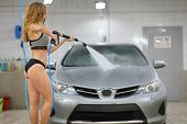 A girl in a swimsuit with a high-pressure hose in her hands washes a car at a car wash poster