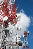 Telecommunications tower with cloudy sky. poster