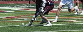 A High School Lacrosse Athlete Is Scooping Up The Ball Off Of The Turf During A Game. poster