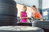 Helpful experienced female auto mechanic checking the identification number of a tire for a customer poster
