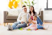 family, holidays and people concept - happy mother, father and little daughter clapping hands at hom poster