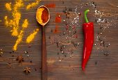Постер, плакат: Spices A Large Wooden Spoon And Red Pepper On A Dark Background Background With Spices spices Top