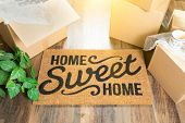 Home Sweet Home Welcome Mat and Moving Boxes on Hard Wood Floor. poster