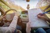Examiner filling in drivers license road test form sitting with her student inside a car poster