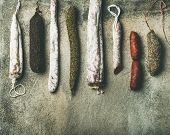 Variety Of Spanish Or Italian Cured Meat Sausages. Flat-lay Of Fuets And Salamies Over Rough Grey Co poster