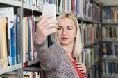 Student Using Mobile Phone For Selfie In Library poster