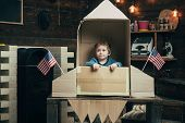 Boy Play With Rocket, Cosmonaut Sit In Usa Rocket Made Out Of Cardboard Box. Kid On Calm Face Sit In poster