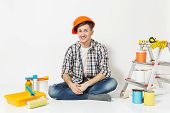 Smiling Man In Orange Protective Helmet Sitting On Floor With Instruments For Renovation Apartment R poster