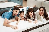 Happy Family Is Relaxing On Mattress In Orthopedic Furniture Store. Big Family Check Softness Of Mat poster